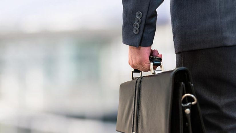Detail of a businessman holding a leather briefcase