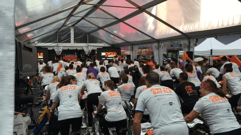 A group of Refinitiv employees cycling in an indoor event and wearing join the battle shirts.