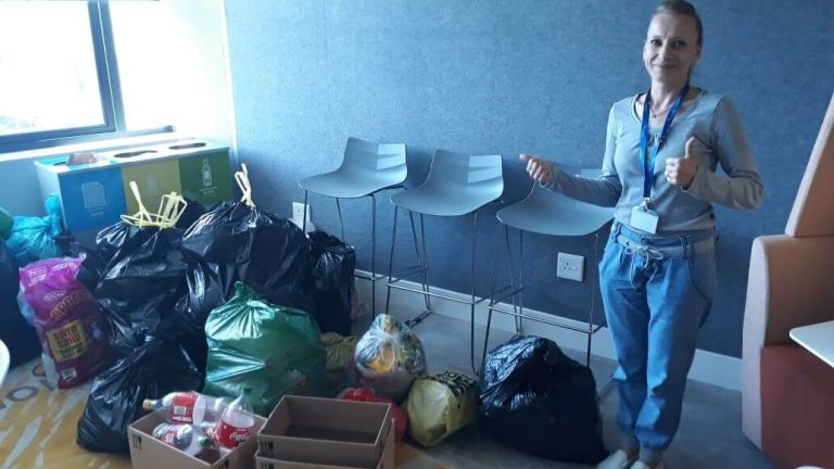 A Refinitiv employee standing by a collection of waste that are placed inside the office to be recycled.