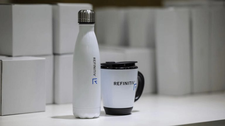A Refinitiv cup and mug presented with boxes in the background.