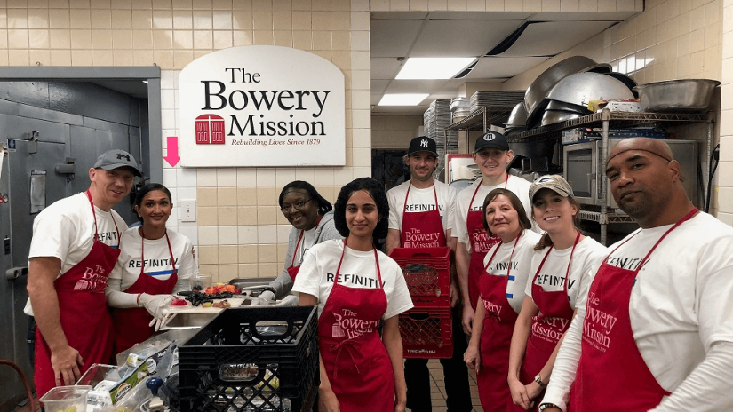 "A group of Refinitiv employees gathered in a kitchen with a large banner behind them stating ""The Bowery Mission."""