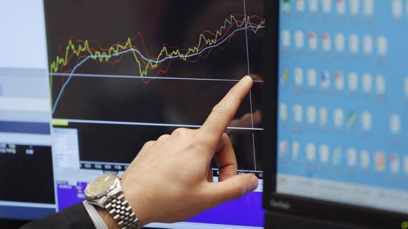 Hand pointing to a financial chart on a screen