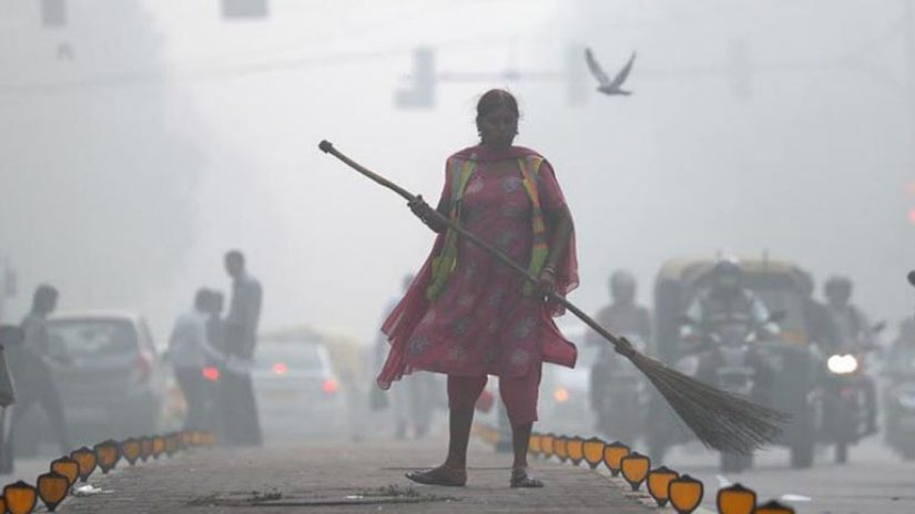 A street cleaner works in heavy smog in Delhi, India