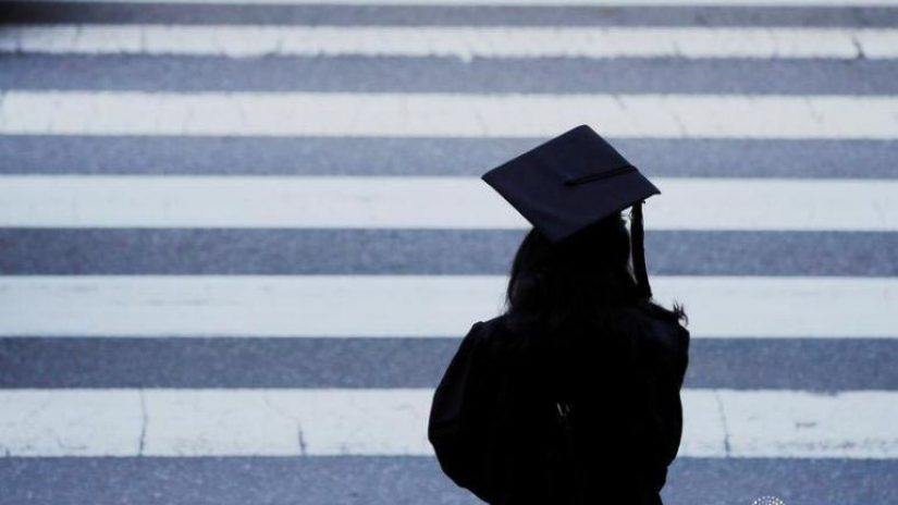A graduating student waits to cross the street before Commencement Exercises at the Massachusetts Institute of Technology